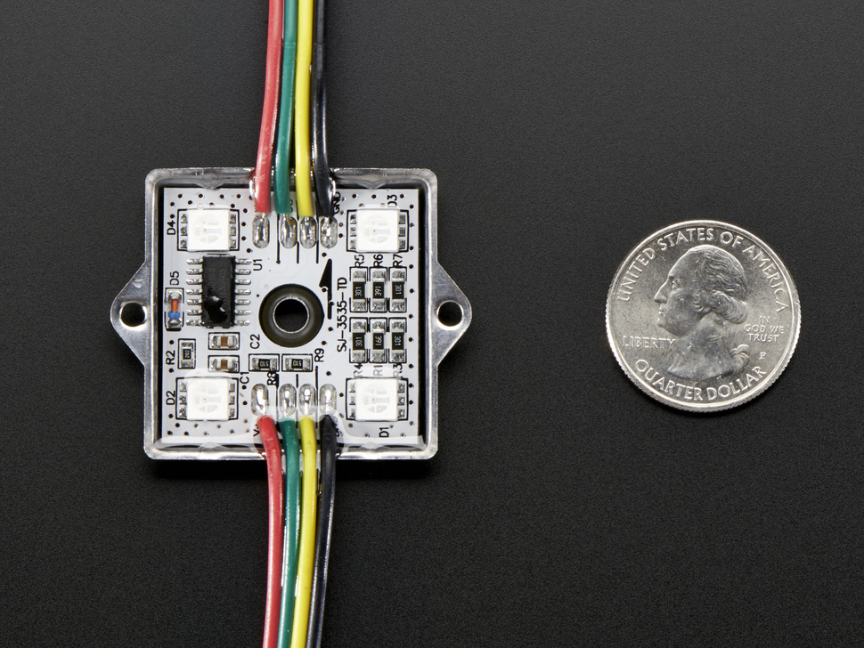 Close up of one pixel square showing components, LEDs and mounting hole, next to quarter