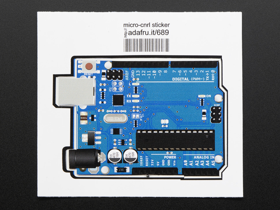 Rectangularish sticker in the shape of arduino uno, in light blue with grey edging and ICU and component details in black and grey. Mounted on white paper with barcode.