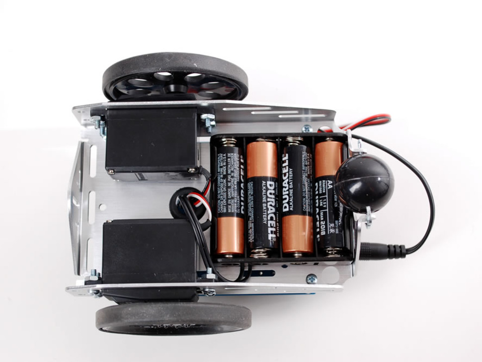 Bottom of robot with two wheels, caster, and 4 AA batteries.