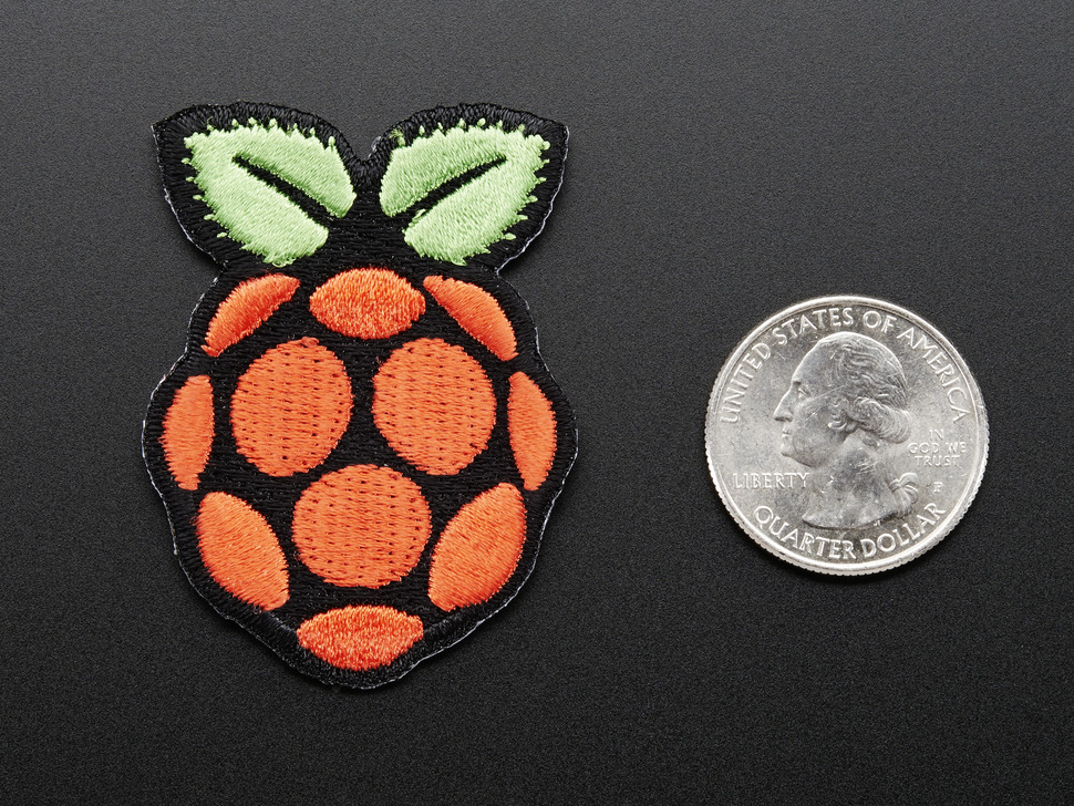 Embroidered patch in the shape of the raspberry pi logo, in red with green leaves on top, outlined in black. Shown next to quarter for scale.