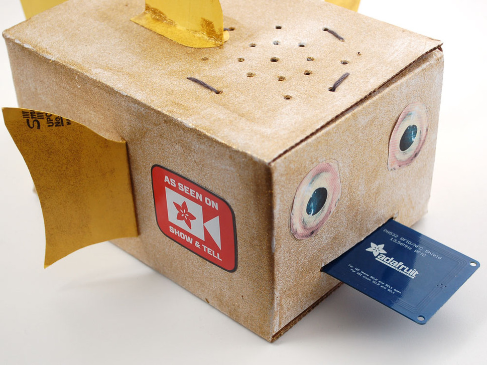 DIY cardboard fish box showing the sticker on the side and an Adafruit subscription card ejected from the mouth.