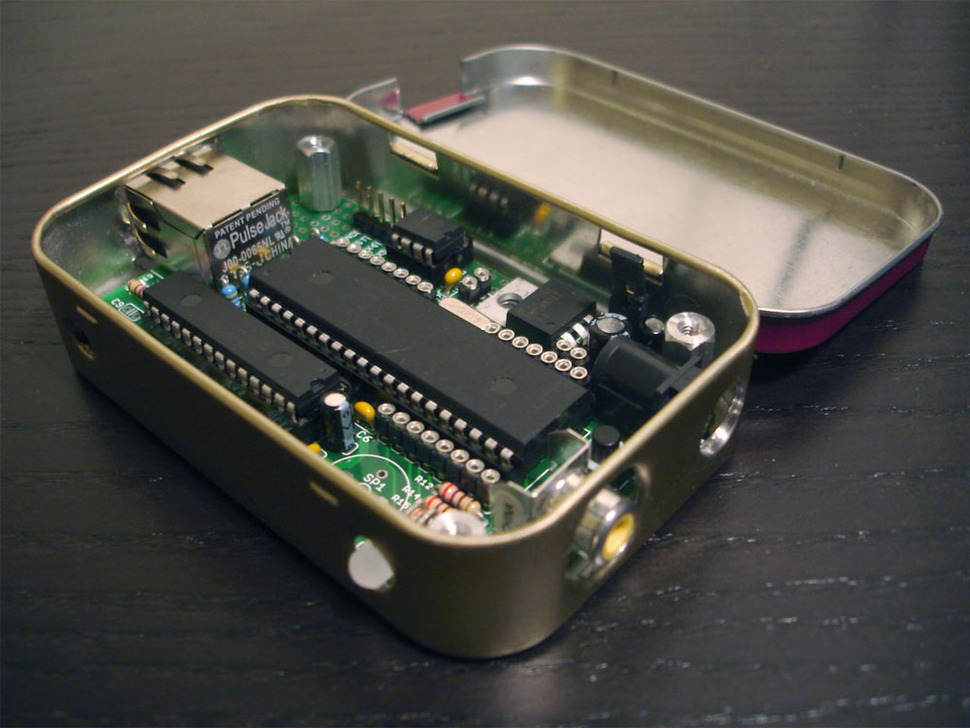 Opened altoids tin, showing assembled YBox kit inside.