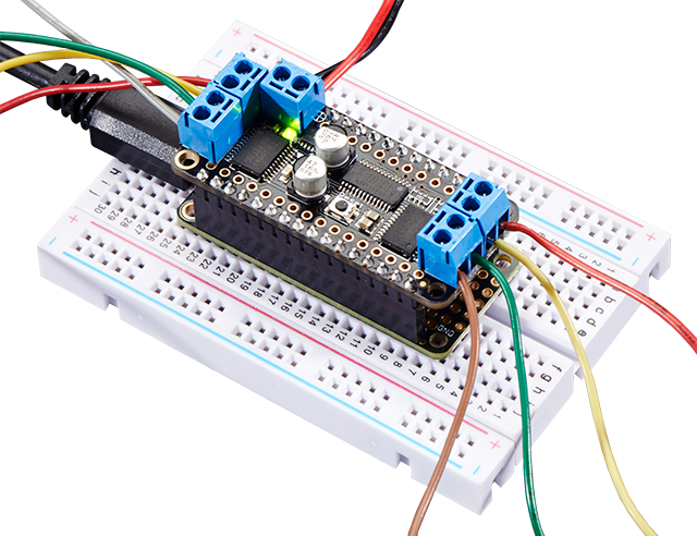 Top view of a DC Motor and Stepper FeatherWing plugged into a white breadboard.