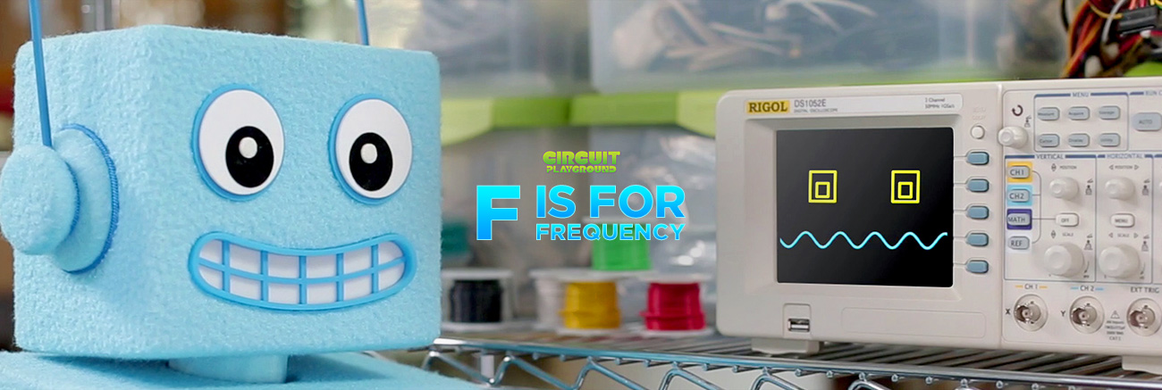 Circuit Playground Episode F is for Frequency. A friendly robot, AdaBot, checks out an oscilloscope on a work shelf. The oscilloscope is powered on. Its face on the digital display has eyes and a squiggly mouth. It is upset or uncomfortable.