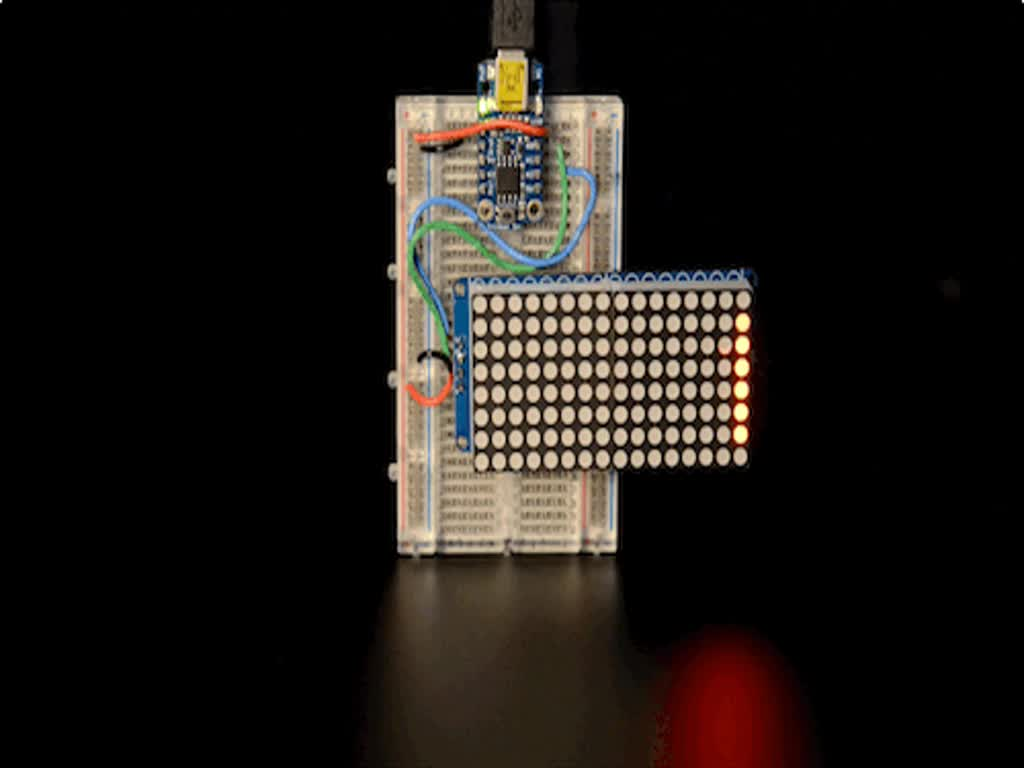 """Soldered and assembled 16x8 1.2"""" LED Matrix + Backpack - Ultra Bright Round Red LEDs on a breadboard powered by a trinket. The LED Matrix displays the rolling text: """"Adafruit"""""""