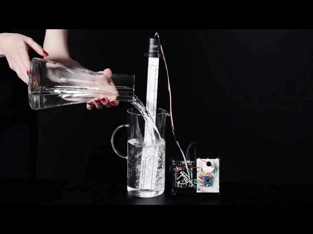 Hand pouring water into tall carafe with water sensor inside it, a gauge increases as more water is poured