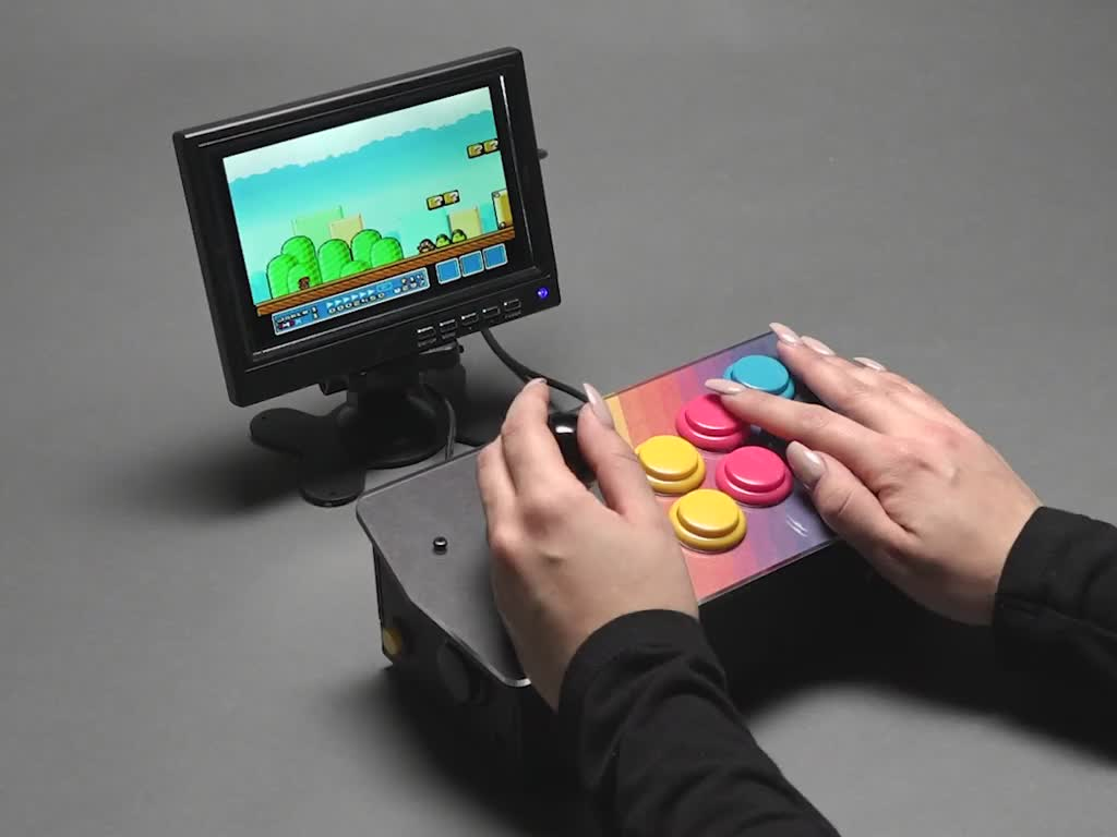 Angled video of two white hands playing Mario World on an assembled Pimoroni Picade Console Controller Kit connected to small monitor.
