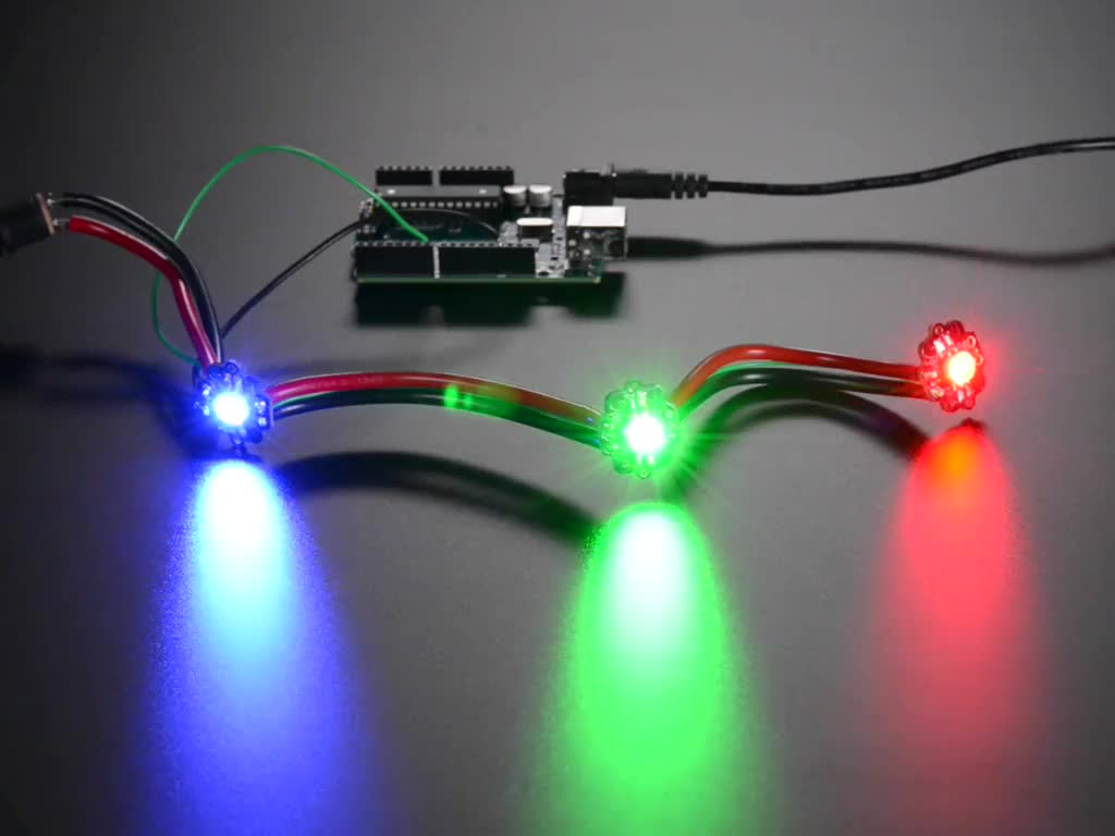 Animation of three very bright chained LEDs all changing rainbow colors