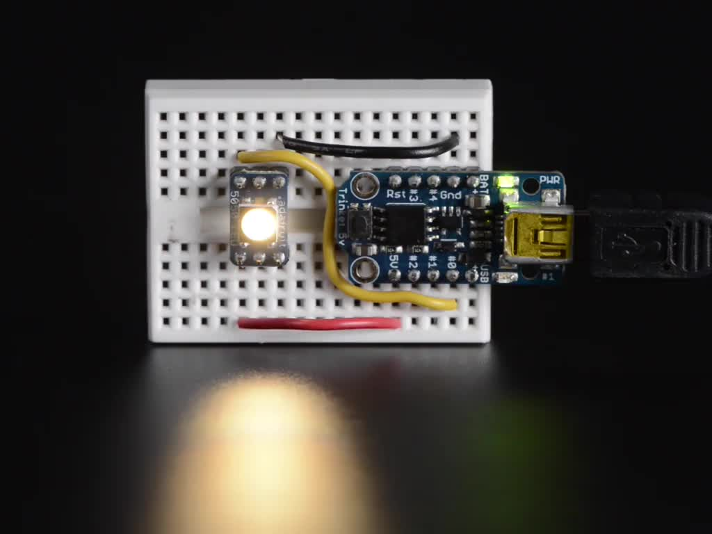 NeoPixel RGBW LED wired up to microcontroller and glowing rainbow and white