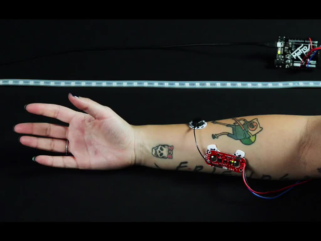 Hand repeatedly squeezing while wired to sensor, an LED strip glows red with each squeeze