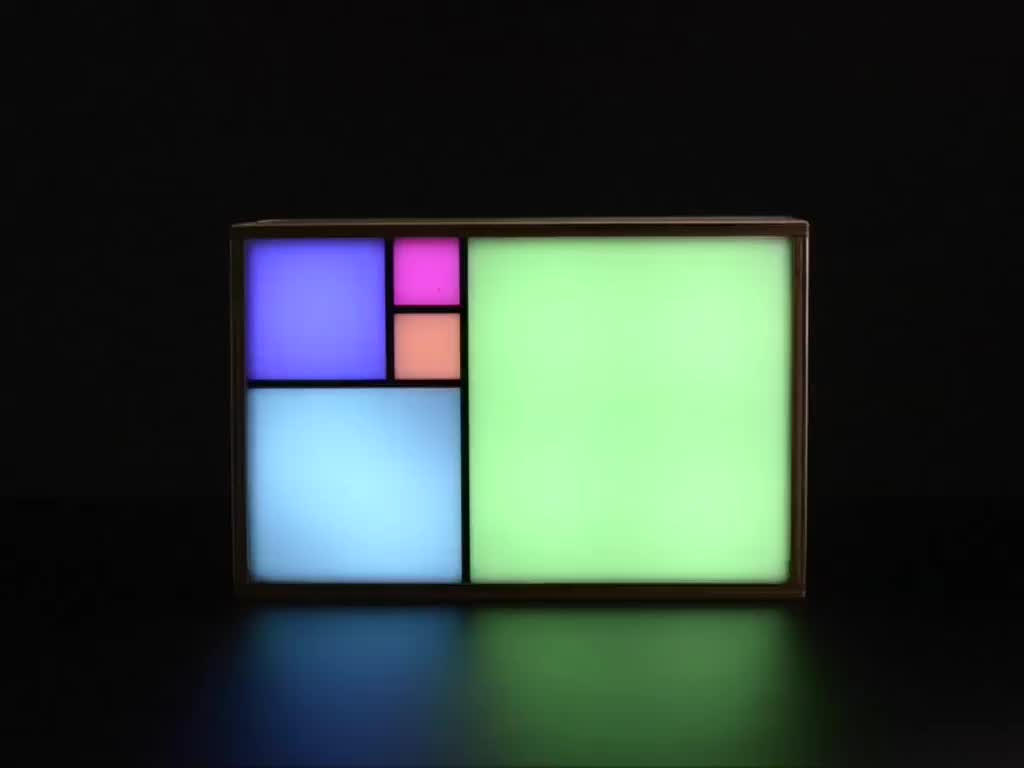 Artistic clock with 5 large squares on front glowing in rainbow colors