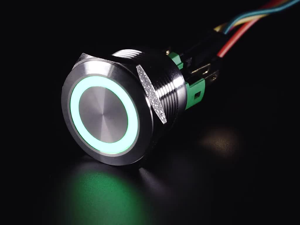 Close-up video of rugged metal pushbutton with an LED ring glowing rainbow colors.
