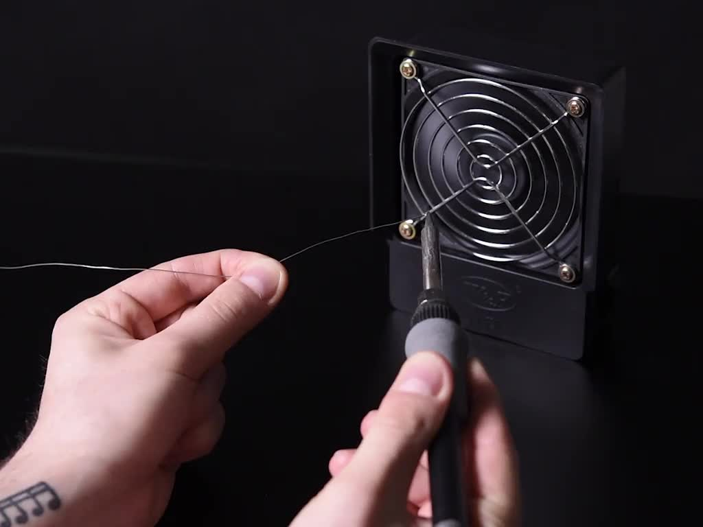 Person using fan to vent away solder smoke