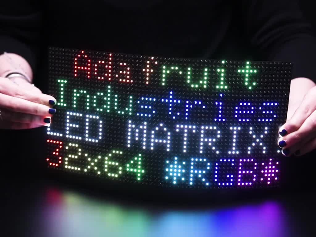 Two hands flexing a powered on 64x32 Flexible RGB LED Matrix - 5mm Pitch.