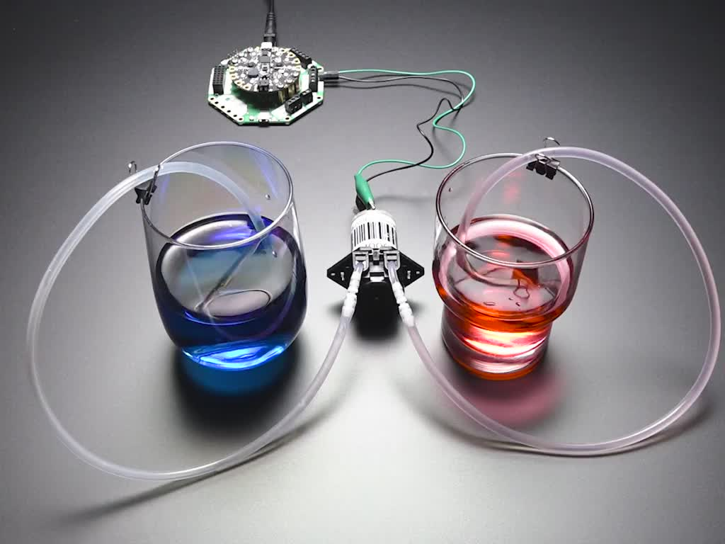 Peristaltic Liquid Pump moving liquid from a red cup to a blue cup