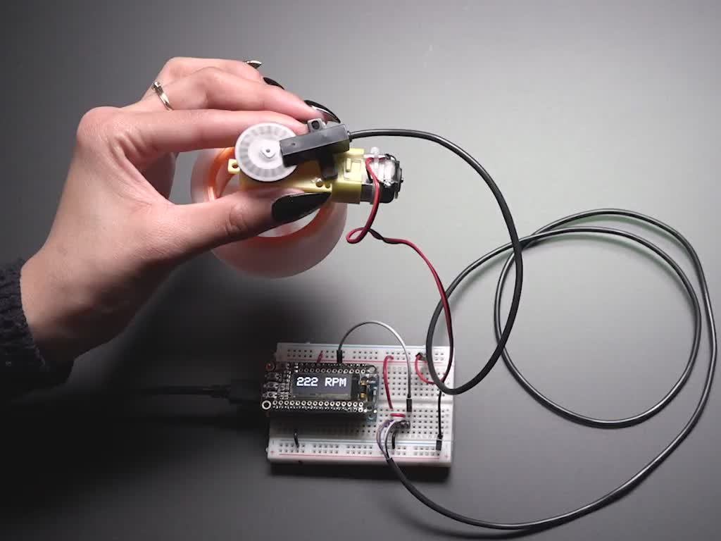 Hand holding motor with spinning wheel. T-slot sensor is attached over an encoder disk and is showing the RPM on an OLED display