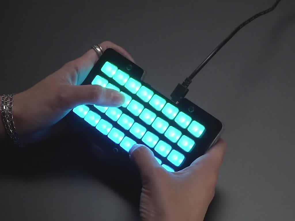 Hands pressing buttons on lit up NeoTrellis M4