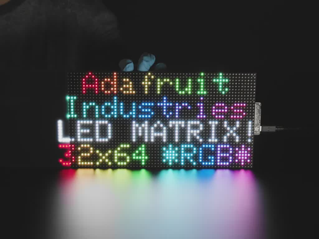 """LED RGB matrix with """"Adafruit Industries LED Matrix"""" text showing, and LED acrylic slowly covering to make it nicely diffused"""