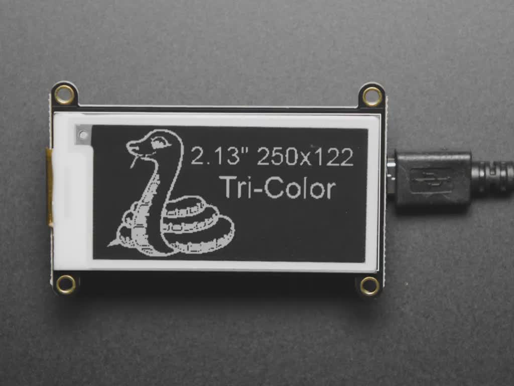 E-Ink display connected to Feather, refreshing itself with image of friendly snake