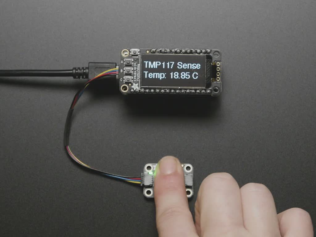 Finger on sensor connected to a Feather via QT cable, with OLED wing showing skin temperature