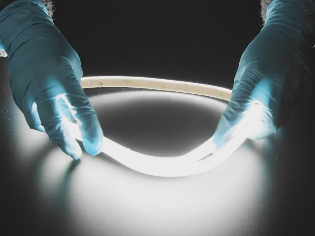 Two hands repeatedly bending and manipulating lit-up flexible LED strip