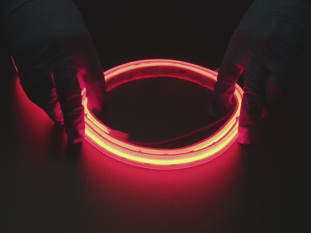 Two hands repeatedly bending and manipulating lit-up flexible red LED strip