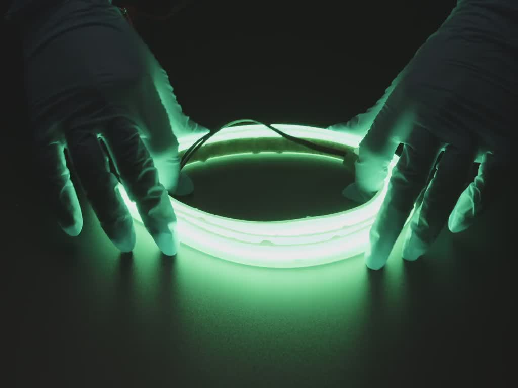 Two hands repeatedly bending and manipulating lit-up flexible green LED strip