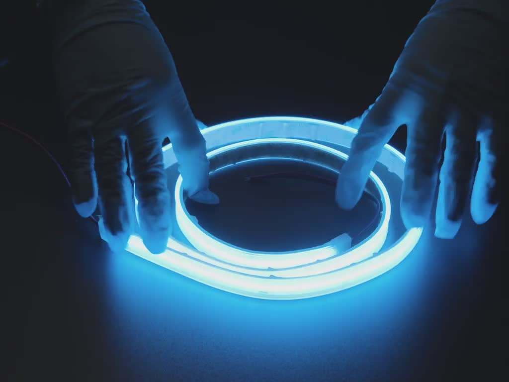 Two hands repeatedly bending and manipulating lit-up flexible blue LED strip
