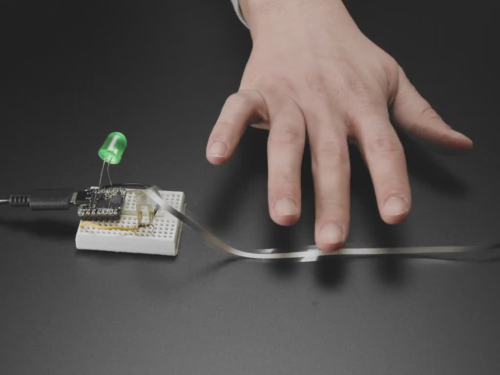 Video of hand tapping the ribbon sensor triggering a green LED installed on a breadboard to light up.