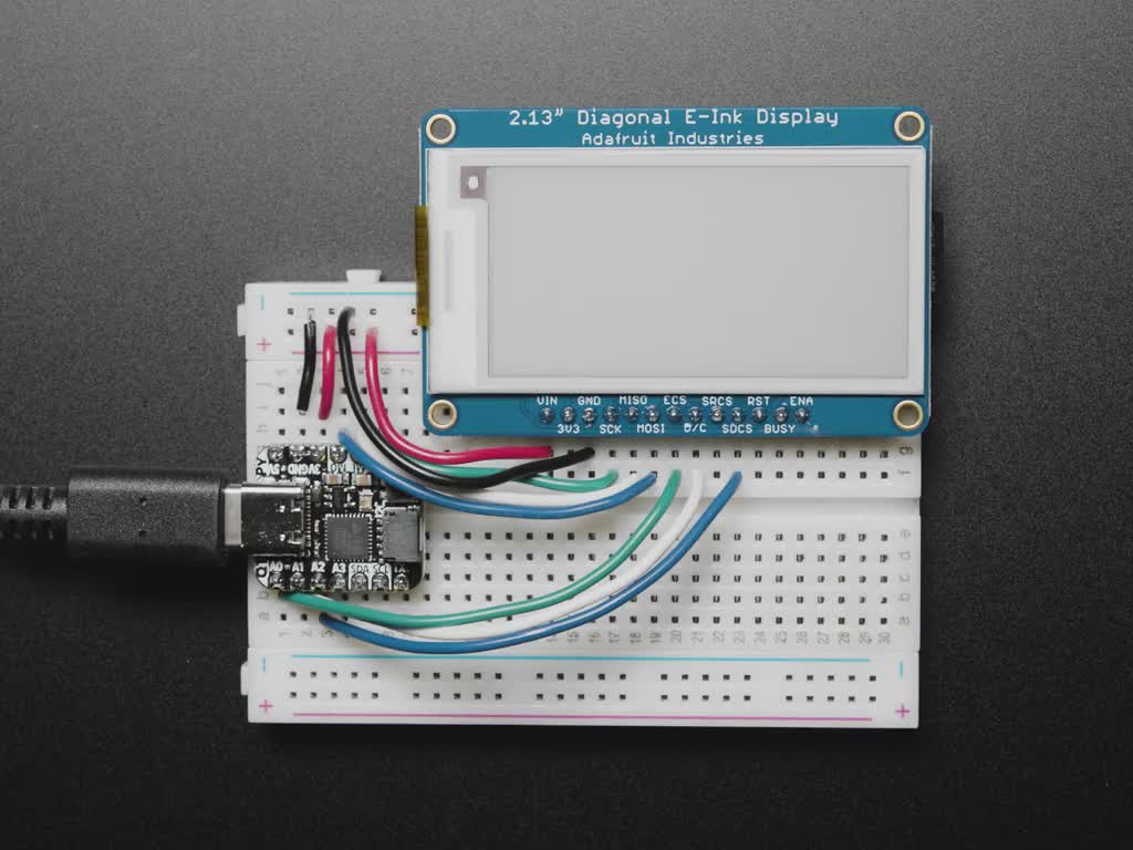 """Video of a 1.54"""" tri-color eInk display assembled on a breadboard with jumper wires and a QT Py. Friendly snake in white-and-red, Blinka, appears on the display."""