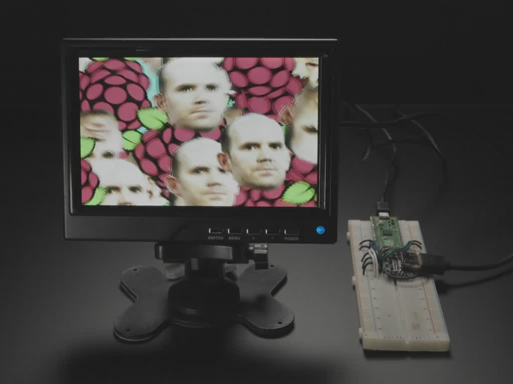 Video of DVI breakout board on breadboard with Raspberry Pico RP2040 hooked up with jumper wires. A small HDMI monitor displays a psychedelic animation with Raspberry Pi logos and bouncing middle-aged white man bust of Raspberry Pi founder.