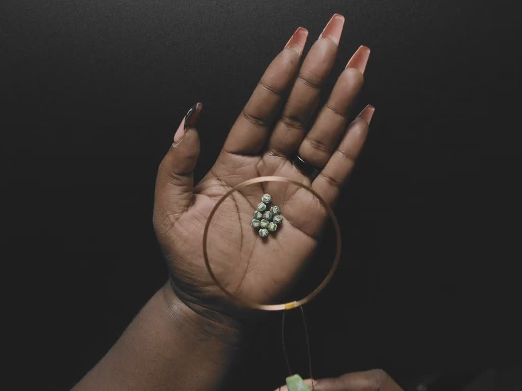 Video of a Black woman holding ten bare LEDs in her hand. She lowers an inductive charger coil down to her hand, lighting up the ten small LEDs.