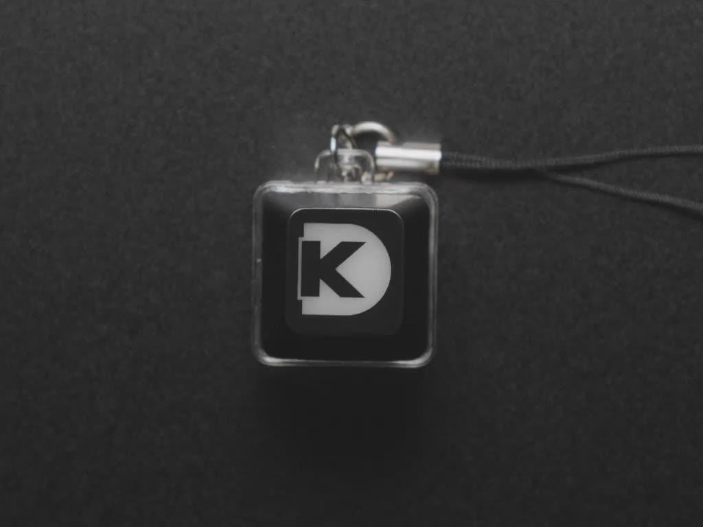 A Black woman's finger presses a keyswitch keychain. A red LED shines beneath a Digi-Key logo keycap.