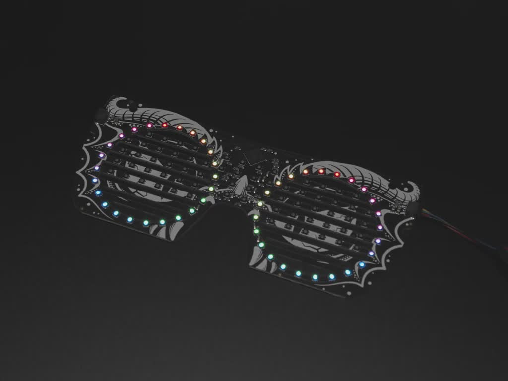 Angled view of dragon eyeglass PCB. ADAFRUIT in rainbow LEDs scrolls across the mask.