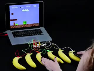 Person playing super mario bros game by touching bananas