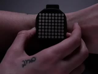 Hand pressing side of a square watch and time scrolls by on orange LED matrix.