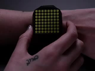 Hand pressing side of a square watch and time scrolls by on white LED matrix.