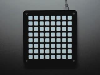 8x8 NeoTrellis with the button lights turning on one by one, in a rainbow