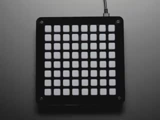 Hand pressing buttons that light up on 8x8 NeoTrellis kit
