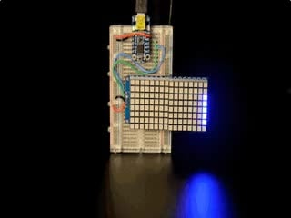 """Soldered and assembled 16x8 1.2"""" LED Matrix + Backpack - Ultra Bright Square Blue LEDs on a breadboard powered by a trinket. The LED Matrix displays the rolling text: """"Adafruit"""""""