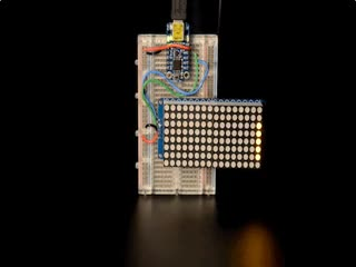 """Soldered and assembled 16x8 1.2"""" LED Matrix + Backpack - Ultra Bright Square Orange LEDs on a breadboard powered by a trinket. The LED Matrix displays the rolling text: """"Adafruit"""""""