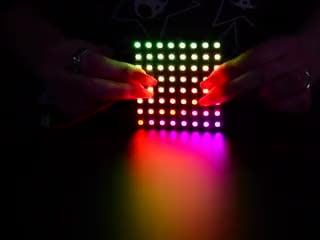 Two hands flexing a rainbow pulsing Flexible Adafruit DotStar Matrix 8x8 - 64 RGB LED Pixels.