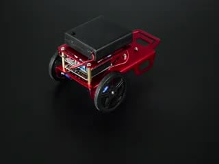 Two-wheeled robot turning around a few times and then driving off.