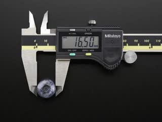 Digital calipers measuring various fruits