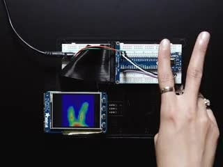 Video of a hand making bunny ears with their fingers over the AMG8833 IR thermal sensor. A thermal image readout displays on a TFT screen wired into a breadboard.
