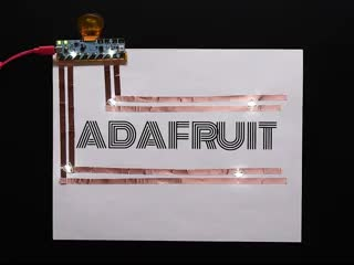 Video of the Chibi Chip attached to a single piece of white paper with four lines of copper tape circuits. ADAFRUIT is in bold lettering along with four LED stickers that light up.