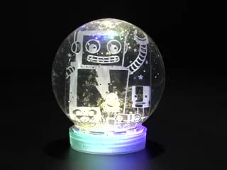 Assembled snow globe kit with glowing electronics and friendly robot inside