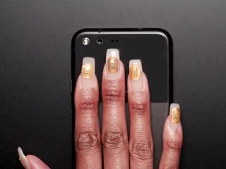 Hand with manicure and tags on naps resting on phone, nails are blinking LEDs.
