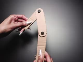 Hand twisting a three-piece hinge made with pop rivents and cardboard