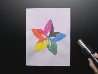 Video of a hand wielding a hot air nozzle over a thermochromic painting of the Adafruit star lotus logo in rainbow colors. The hot air causes the thermochromic paint to disappear into white.